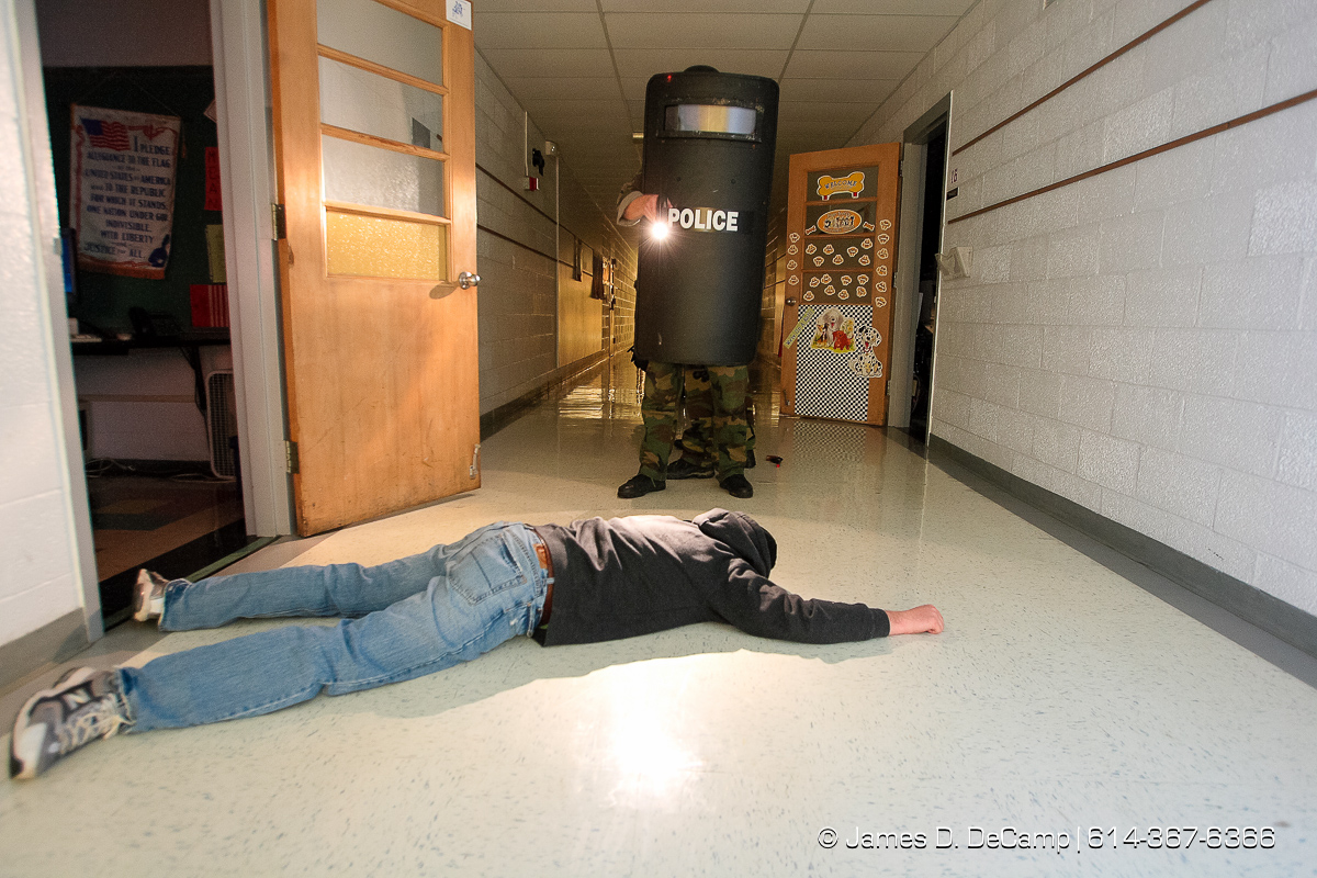 'Wounded suspect' Craig Harman lays on the floor of Etna Elementary School as Whitehall Police SWAT officers make a sweep of rooms and hallways during training late Tuesday night November 28, 2006. The SWAT team tries to hold monthly training sessions of varying degrees and Tuesday nights session was a little more detailed and lasted about 8 hours. The main scenario featured several bank robbery suspects that took refuge in the school, barricaded themselves and took hostages. Negotiations with the suspects took more than 2 hours before SWAT was able to take control of the situation and rescue the hostages. No children where in the school at the time of the drills. Harman is an Army Staff Sergeant who is a recruiter based in Whitehall and several other Army buddies volunteered to be suspects in the monthly training excursive that included the hostage taking scenario and several rounds of 'hide & seek'. NEED MORE INFORMATION: call Whitehall Detective (and SWAT officer) Todd Horning 246-7420 office, 205-7254 cell. (© James D. DeCamp | http://www.JamesDeCamp.com | 614-367-6366) [Photographed with Canon 1D MkII cameras in RAW mode with L series lenses]