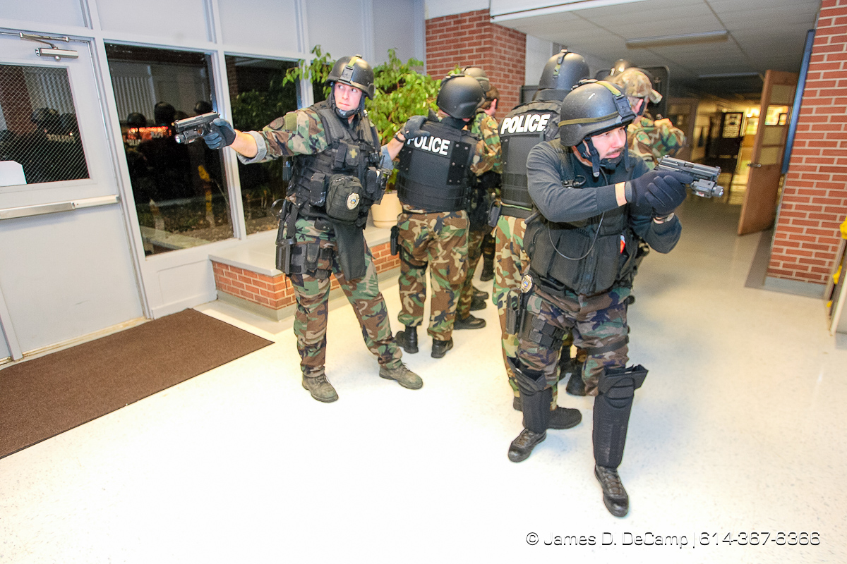 Scott Miller, left, and Rex Adkin, right, watch for suspects as the Whitehall Police SWAT team make a sweep of rooms and hallways of Etna Elementary School during training late Tuesday night November 28, 2006. The SWAT team tries to hold monthly training sessions of varying degrees and Tuesday nights session was a little more detailed and lasted about 8 hours. The main scenario featured several bank robbery suspects that took refuge in the school, barricaded themselves and took hostages. Negotiations with the suspects took more than 2 hours before SWAT was able to take control of the situation and rescue the hostages. No children where in the school at the time of the drills. Harman is an Army Staff Sergeant who is a recruiter based in Whitehall and several other Army buddies volunteered to be suspects in the monthly training excursive that included the hostage taking scenario and several rounds of 'hide & seek'. NEED MORE INFORMATION: call Whitehall Detective (and SWAT officer) Todd Horning 246-7420 office, 205-7254 cell. (© James D. DeCamp | http://www.JamesDeCamp.com | 614-367-6366) [Photographed with Canon 1D MkII cameras in RAW mode with L series lenses]