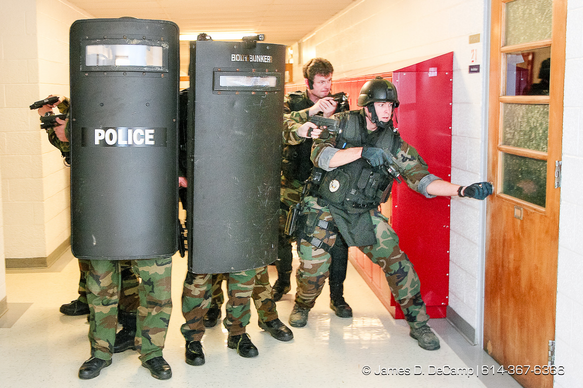 Scott Miller, right, opens a classroom door to make entry as other officers watch for suspects as the Whitehall Police SWAT team make a sweep of rooms and hallways of Etna Elementary School during training late Tuesday night November 28, 2006. The SWAT team tries to hold monthly training sessions of varying degrees and Tuesday nights session was a little more detailed and lasted about 8 hours. The main scenario featured several bank robbery suspects that took refuge in the school, barricaded themselves and took hostages. Negotiations with the suspects took more than 2 hours before SWAT was able to take control of the situation and rescue the hostages. No children where in the school at the time of the drills. Harman is an Army Staff Sergeant who is a recruiter based in Whitehall and several other Army buddies volunteered to be suspects in the monthly training excursive that included the hostage taking scenario and several rounds of 'hide & seek'. NEED MORE INFORMATION: call Whitehall Detective (and SWAT officer) Todd Horning 246-7420 office, 205-7254 cell. (© James D. DeCamp | http://www.JamesDeCamp.com | 614-367-6366) [Photographed with Canon 1D MkII cameras in RAW mode with L series lenses]