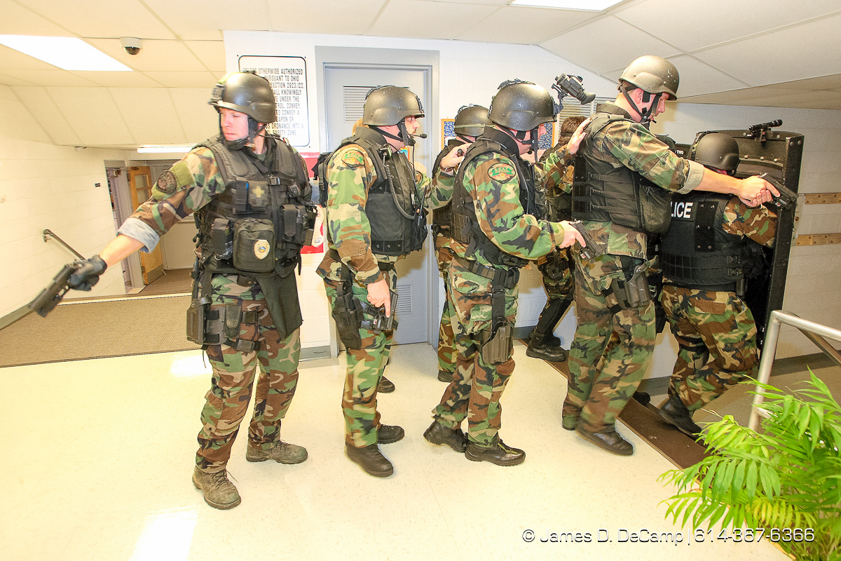 The Whitehall Police SWAT team makes a sweep of rooms and hallways of Etna Elementary School during training late Tuesday night November 28, 2006. The SWAT team tries to hold monthly training sessions of varying degrees and Tuesday nights session was a little more detailed and lasted about 8 hours. The main scenario featured several bank robbery suspects that took refuge in the school, barricaded themselves and took hostages. Negotiations with the suspects took more than 2 hours before SWAT was able to take control of the situation and rescue the hostages. No children where in the school at the time of the drills. Harman is an Army Staff Sergeant who is a recruiter based in Whitehall and several other Army buddies volunteered to be suspects in the monthly training excursive that included the hostage taking scenario and several rounds of 'hide & seek'. NEED MORE INFORMATION: call Whitehall Detective (and SWAT officer) Todd Horning 246-7420 office, 205-7254 cell. (© James D. DeCamp | http://www.JamesDeCamp.com | 614-367-6366) [Photographed with Canon 1D MkII cameras in RAW mode with L series lenses]