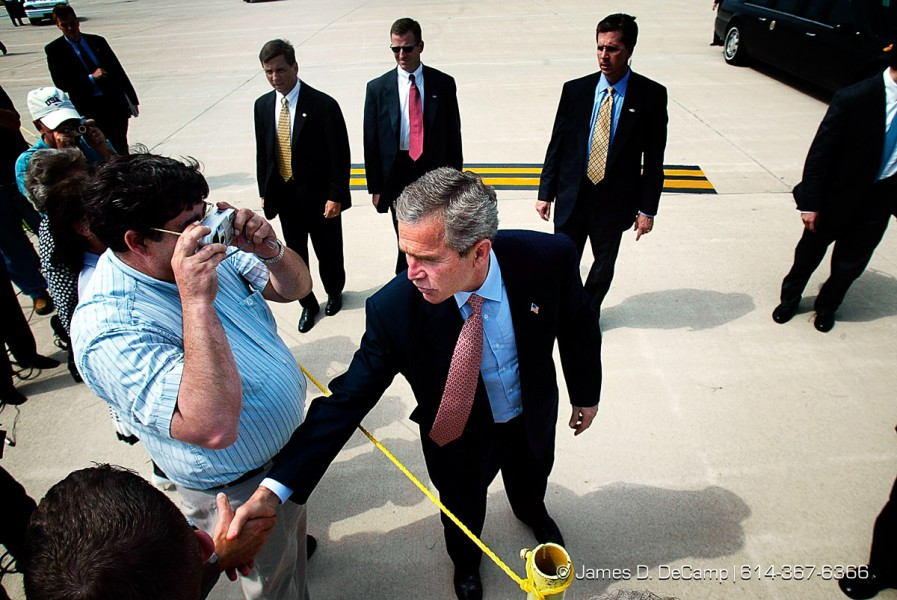 President George Bush greets people at rope line on the tarmac near Air Force One at Port Columbus International Airport Friday morning June 14, 2002 after he attended the Ohio State University Commencement ceremony. Shooting the photo on the left is Alan Cook, Maintenance Supervisor for Raytheon Aerospace. Many Reporters. (© James D. DeCamp 614-367-6366)