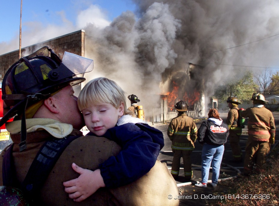 "(JDD WHFIRE 01 11/11/98)  Whitehall Firefighter/Paramedic Mark Soder (cq) hugs and kisses his son, Bailey (cq), 3,  as he and other firefighters watch there station house burn in a controlled fire. Soder told his son ""In that window is where daddy used to watch TV, and over there is were daddy slept."" as they watched the final moments of the Whitehall Fire Station going up in flames Wednesday morning.  The fire station was used for training for Whitehall, Violet, Truro, Columbus, and DSCC this week andwas allowed to burn to the ground to make way for a new fire station on the same location.   Ground is supposed to be broken for the new station on Friday with construction starting next week.  (© James D. DeCamp 614-367-6366)"