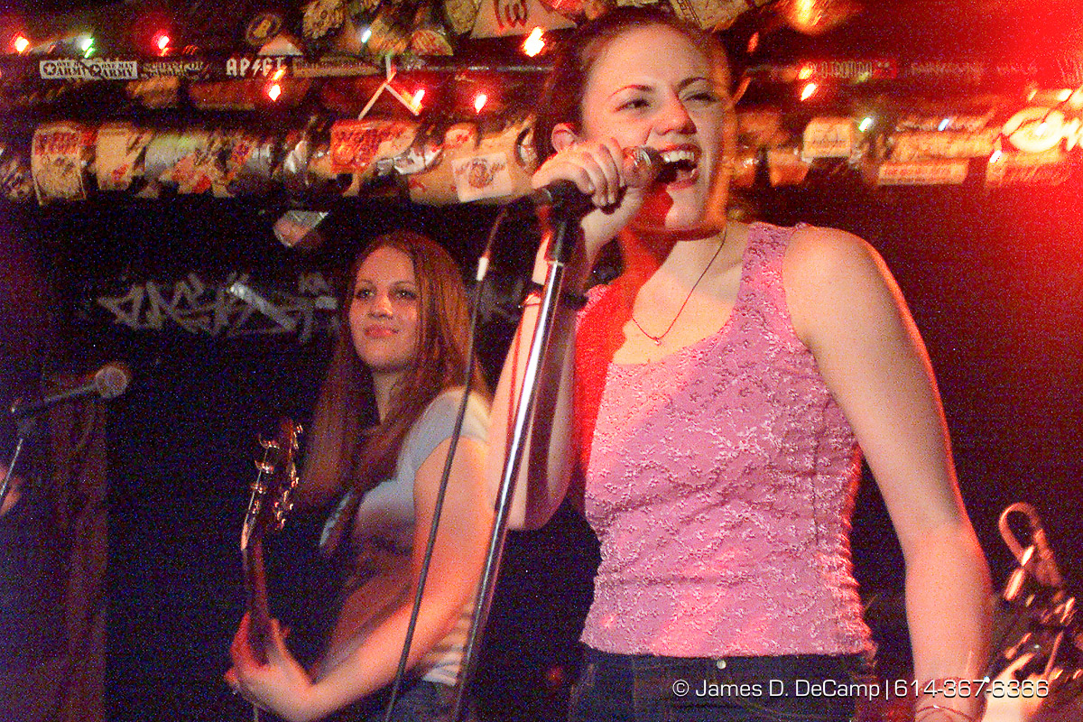 The Donnas (or at least two out of four of them shown here) take the stage at Bernie's on High Street in the campus area Tuesday night March 21, 2000. (© James D. DeCamp | http://www.JamesDeCamp.com | 614-367-6366) [Photographed with Canon EOS D2000 cameras in RAW mode with L series lenses.]