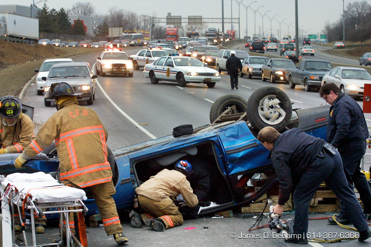 Columbus Firefighters and Paramedics work to dismantle the car of an unidentified woman who was trapped after she flipped her car on I-71 southbound just north of Hudson Street at about 5:45 PM Thursday March 8, 2001. The victim was transported by Medic 16 to the hospital (I think Grant - not sure). I-71 southbound was shut down for nearly an hour as rescue workers cut apart her car and extricated her. Columbus Police Sgt. McConnell has the report. (© James D. DeCamp | http://www.JamesDeCamp.com | 614-367-6366) [Photographed with Canon EOS D30 cameras with L series lenses.]