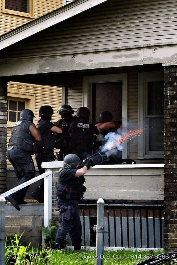 A Columbus Police Narcotics Tactical officer fires a