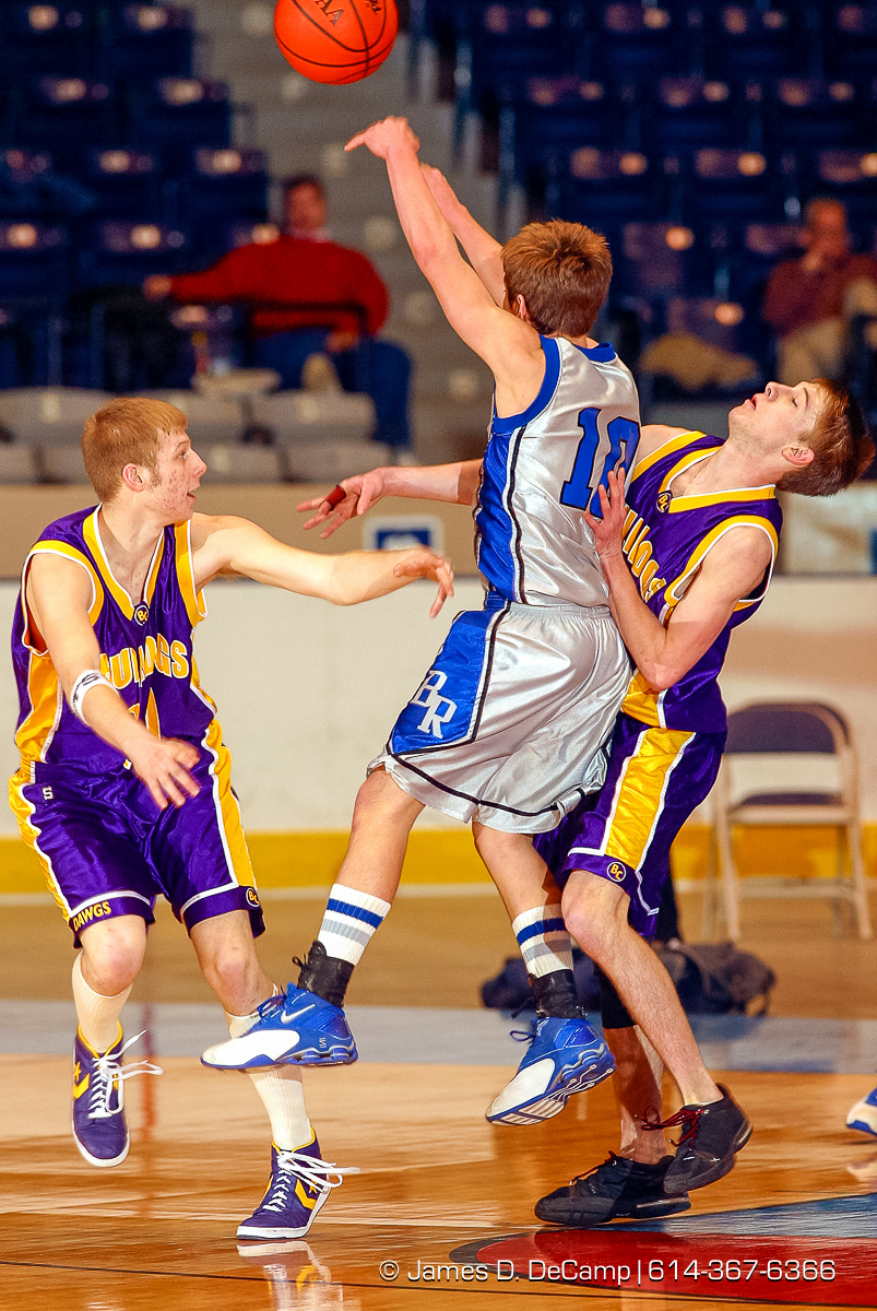 Bloom Carroll High School's #10 Joe Goodyear, left, and #3 Eric Baughman, right, guard Bishop Ready High School's #10 Mackie McAndrew, center, in the first quarter of play of the Ohio High School Athletic Association's Division III Central District Boys Basketball Tournament held at the Ohio Expo Center and Fairgrounds Coliseum Thursday March 11, 2004. (© James D. DeCamp | http://www.JamesDeCamp.com | 614-367-6366) [Photographed with Canon D60 cameras in RAW mode with L series lenses]