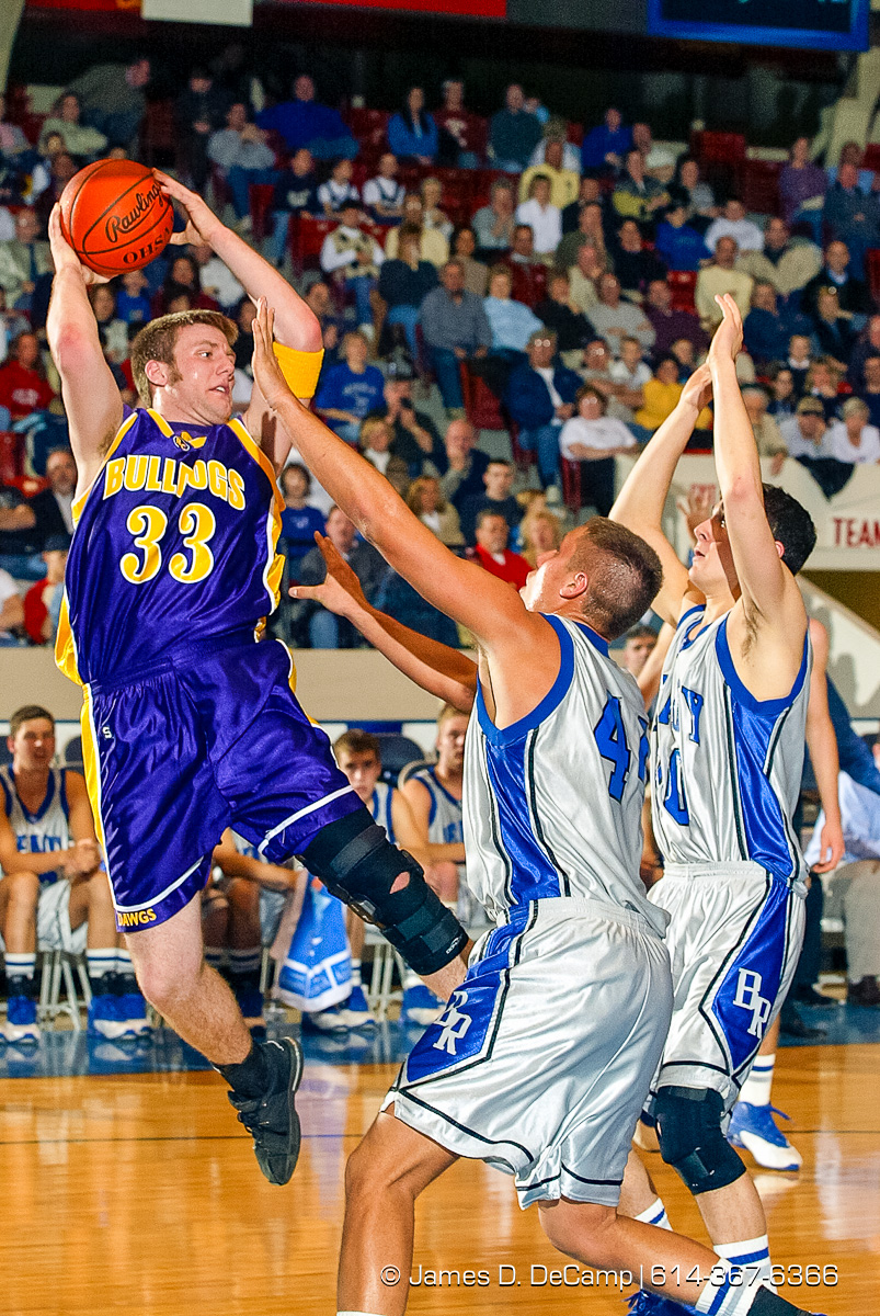 Bloom Carroll High School's #33 Ron Ball, left, drives past Bishop Ready High School's #44 Casey Brown, and #30 Justin Clark, right, for two points in the second quarter of play of the Ohio High School Athletic Association's Division III Central District Boys Basketball Tournament held at the Ohio Expo Center and Fairgrounds Coliseum Thursday March 11, 2004. (© James D. DeCamp | http://www.JamesDeCamp.com | 614-367-6366) [Photographed with Canon 1D MkII cameras in RAW mode with L series lenses]