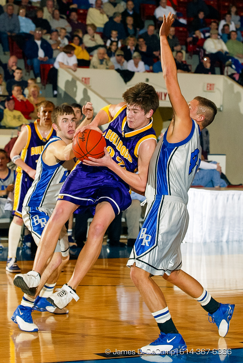 Bloom Carroll High School's #32 Kale Richardson, left,guards Bishop Ready High School's #32 Dustin Dilley, rear, and #44 Casey Brown, right, in the first quarter of play of the Ohio High School Athletic Association's Division III Central District Boys Basketball Tournament held at the Ohio Expo Center and Fairgrounds Coliseum Thursday March 11, 2004. (© James D. DeCamp | http://www.JamesDeCamp.com | 614-367-6366) [Photographed with Canon 1D MkII cameras in RAW mode with L series lenses]