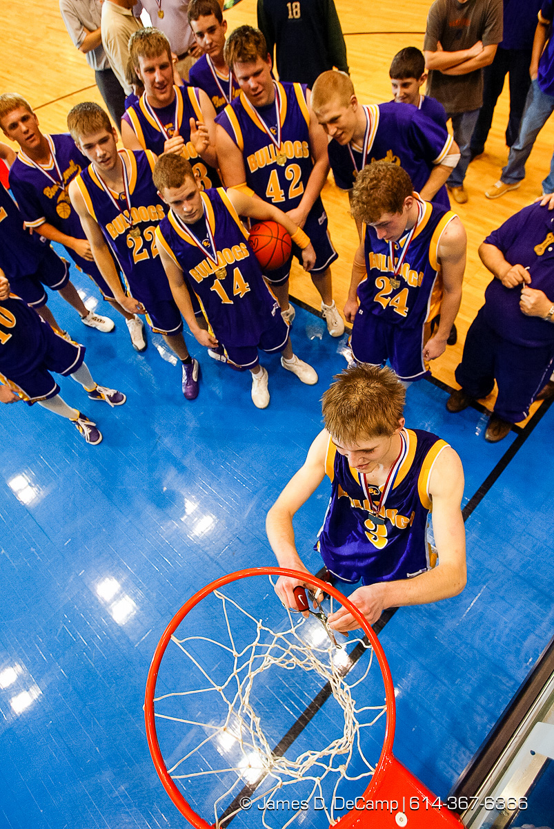 Bloom Carroll High School's #3 Eric Baughman, bottom, cuts away part of the winning net following their win over Bishop Ready High School in the Ohio High School Athletic Association's Division III Central District Boys Basketball Tournament held at the Ohio Expo Center and Fairgrounds Coliseum Thursday March 11, 2004. (© James D. DeCamp | http://www.JamesDeCamp.com | 614-367-6366) [Photographed with Canon 1D MkII cameras in RAW mode with L series lenses]