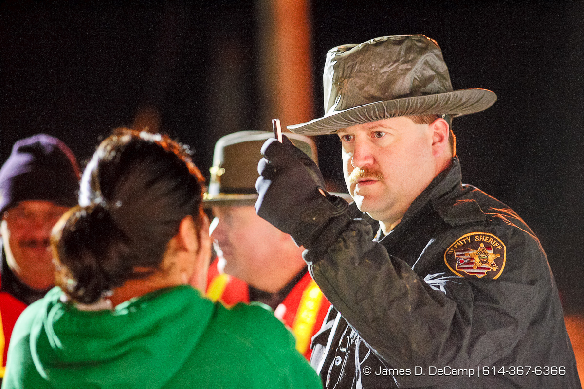 As part of a Franklin County DUI task force crack down on drunken drivers Franklin County Sheriff Deputy Matt Reed watches a subjects eyes as she following his pen at a sobriety check point in Franklin Township, at the just east of the intersection of Frank Road and U.S. Route 62 in the early morning hours of Saturday March 18, 2006. The female, who declined to give her name, was found to be 'borderline', while she was showing some signs of impairment, the officers did not feel that they had enough evidence to prosecute her and allowed a friend to come and pick her up. Several dozen officers took part in the St. Patricks Day event. (© James D. DeCamp | http://www.JamesDeCamp.com | 614-367-6366) [Photographed with Canon 1D MkII cameras in RAW mode with L series lenses]