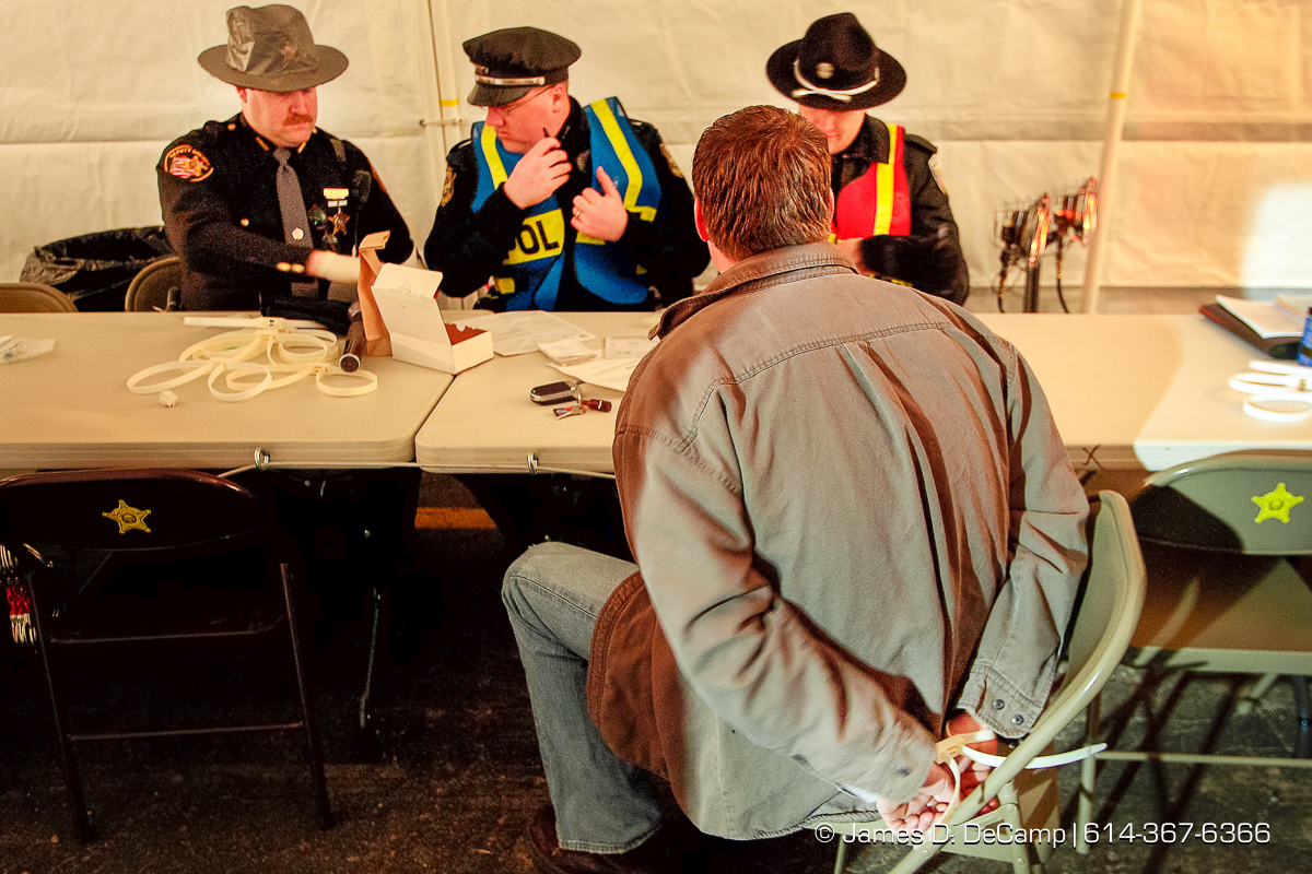 Timothy C. Carr, Jacksonville, Ohio, sits handcuffed as he is processed during part of a Franklin County DUI task force crack down on drunken drivers at a sobriety check point in Franklin Township, at the just east of the intersection of Frank Road and U.S. Route 62 in the early morning hours of Saturday March 18, 2006. two opened 24 packs of beer, more than a dozen empty cans, and several half full cans of beer were found strewn around the interior of Carr's SUV. Several dozen officers took part in the St. Patricks Day event. (© James D. DeCamp | http://www.JamesDeCamp.com | 614-367-6366) [Photographed with Canon 1D MkII cameras in RAW mode with L series lenses]