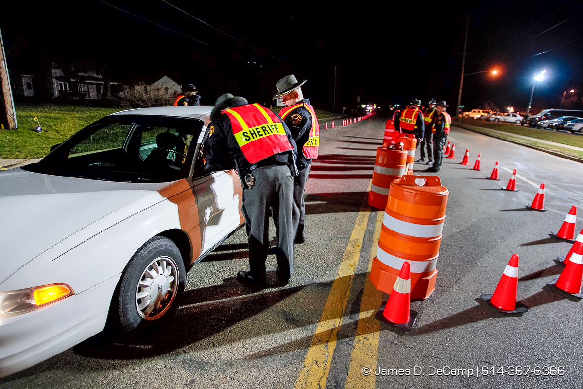 As part of a Franklin County DUI task force crack down on drunken drivers Franklin County Sheriff Deputies check a car at a sobriety check point in Franklin Township, at the just east of the intersection of Frank Road and U.S. Route 62 in the early morning hours of Saturday March 18, 2006. Several dozen officers took part in the St. Patricks Day event. (© James D. DeCamp | http://www.JamesDeCamp.com | 614-367-6366) [Photographed with Canon 1D MkII cameras in RAW mode with L series lenses]