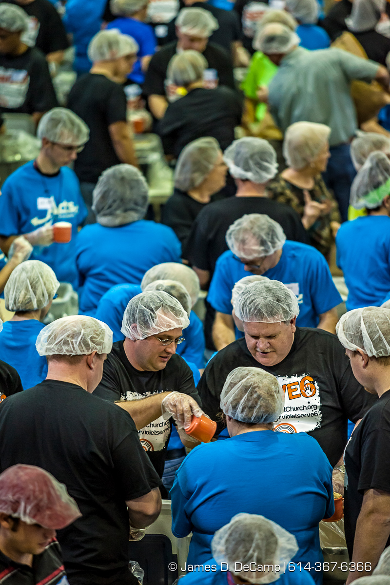 Brian Naess, left, and Steve Hopkins, right, from the Violet Baptist Church and more than 350 other volunteers pack an estimated 80,000 food bags at the Violet Baptist Church Sept. 29.  The food bags will be distributed by the Stop Hunger Now organization to more than 70 different countries around the world. (© James D. DeCamp | http://www.JamesDeCamp.com | 614-367-6366)