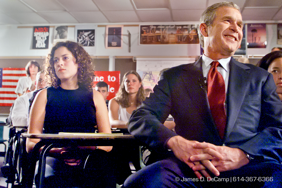 Republican presidential candidate Texas Gov. George W. Bush turns and laughs at the national media pool as he sits in a classroom at Westerville South High School in Westerville, Ohio. Bush was watching his wife on C-SPAN giving a speech at the Republican National Convention in Philadelphia Monday night July 31, 2000. On the left is Kate Madsen, who will be a senior at Westerville South High in the fall. The 24 students were hand picked to be in the photo op with the candidate. (© James D. DeCamp | http://www.JamesDeCamp.com | 614-367-6366) [Photographed with Canon EOS D2000 cameras in RAW mode with L series lenses.]
