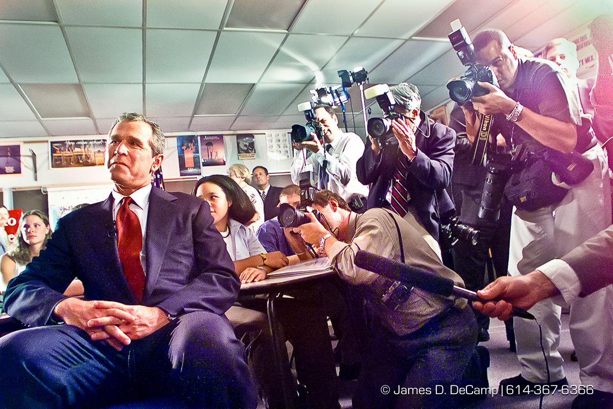 Republican Presidential candidate George Bush sits in a classroom at Westerville South High School and watches his wife on C-SPAN giving a speech at the Republican National Convention in Philadelphia. The backdrop to Bush is the national press corps on the right, and students from Westerville South on the right. The 24 students were hand picked to be in the photo op with the candidate. (© James D. DeCamp | http://www.JamesDeCamp.com | 614-367-6366) [Photographed with Canon EOS D2000 cameras in RAW mode with L series lenses.]