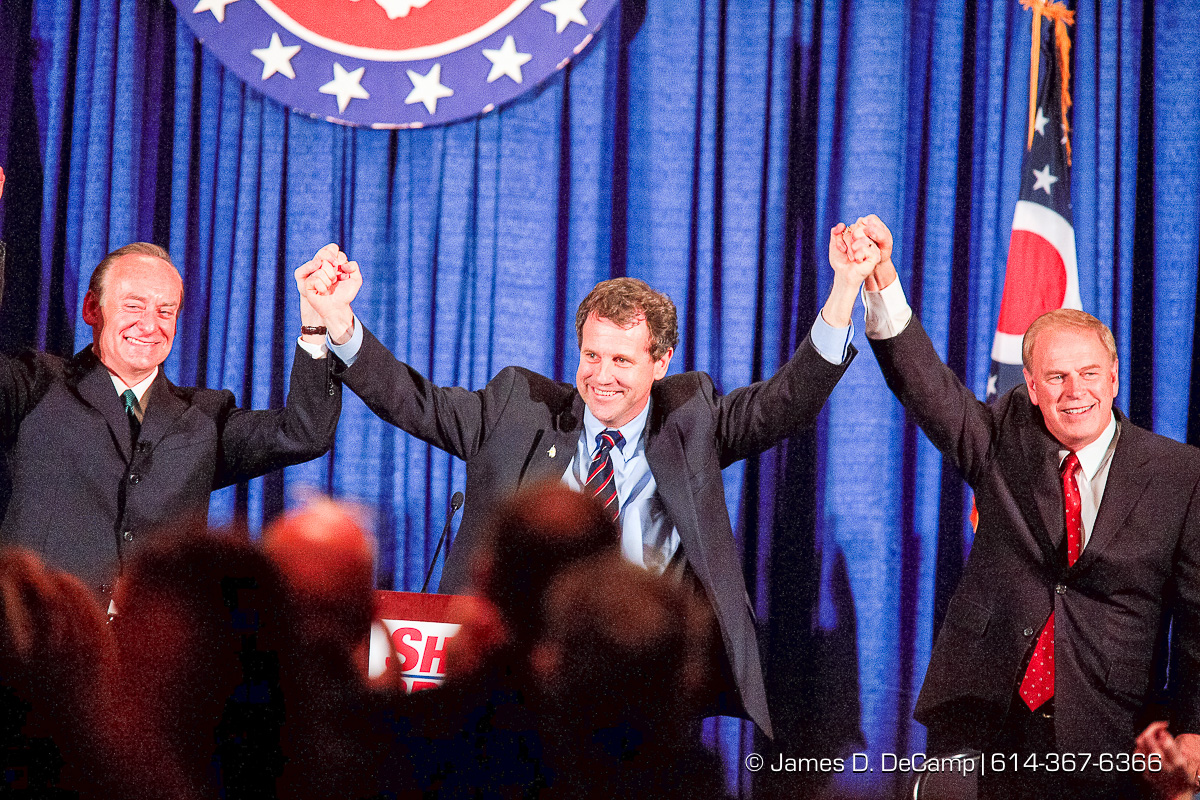 Senate Candidate Sherrod Brown, center raises the hands of Lee Fisher, left, and Ted Strickland right, at a Democratic fundraiser for himself which featured Former President Bill Clinton held at the Hyatt on Capitol Square Monday night October 23, 2006. (© James D. DeCamp | http://www.JamesDeCamp.com | 614-367-6366) [Photographed with Canon 1D MkII cameras in RAW mode with L series lenses]