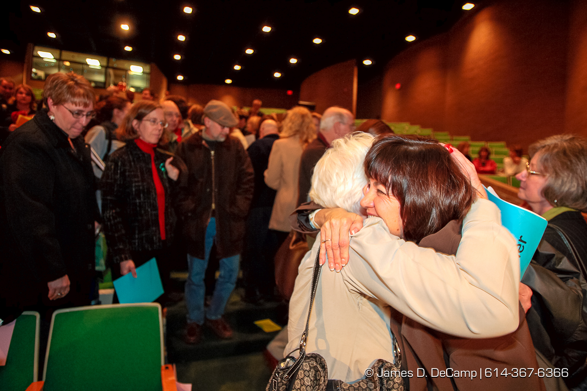 """Dr. Linda Fenner, right, in dark coat, gets a hug from former co-worker and friend Connie Barth, in white coat, after being fired at a regular meeting of the Dublin Board of Education held at Dublin Coffman High School's Performing Arts Center Tuesday night December 12, 2006. The agenda for Tuesday night's school board meeting includes two resolutions about Superintendent Linda Fenner and Treasurer Chris Mohr: one to extend their contracts and the other to declare that the board does not intend to retain them.  The dueling resolutions reflect the fallout after Fenner and Mohr's once-close relationship disintegrated. Complaints that each filed against the other revealed an instance where they kissed, gushy e-mails Fenner sent Mohr, and the intertwining of their personal and work relationships.  Since then, critics have questioned their professionalism while others have stood up to support Mohr or Fenner. """"I fear here that what's happened is there has been such a public outcry that the board believes that the easiest way out is just to nonrenew both of them,"""" said Mohr's attorney, Rex Elliott.  Fenner's attorney, John Marshall, said the opposite, at least about her fate. """"It's pretty clear that there is enormous support for Dr. Fenner in the community. Actually, if it comes to a vote, I'd be surprised if she's not renewed."""" Fenner has said that she has no intention of resigning. School board President Chris Valentine wouldn't say what the board would do Tuesday but said the members were eager """"to put the focus back on the students and the education we provide them."""" """"The board is evaluating all of these factors. Ultimately, this is a very difficult decision.""""  If the board decides to nonrenew either or both officials, they would serve the remainder of their contracts, Valentine said. Fenner's contract expires in July; Mohr has 13 months left on his, Valentine said.  (© James D. DeCamp 