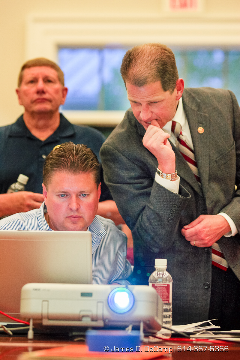 Mike Klein, bottom left, and New Albany Schools Superintendent Steve Castle watch election returns projected on a screen at the New Albany High School Tuesday night May 8, 2007. In the rear left is School Board VP George Stribick. New Albany residents where voting on a $34,000,000.00 bond issue in todays election which would allow the school district to build a new school and gym facility for the district. The issue failed to pass. (© James D. DeCamp | http://www.JamesDeCamp.com | 614-367-6366) [Photographed with Canon 1D MkII cameras in RAW mode with L series lenses]