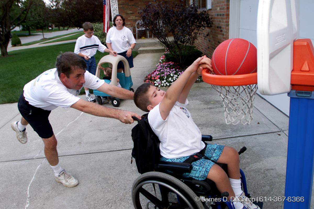 "Jeff Caldwell, left, wheels his son Alex, 9, right, up to a basketball hoop in their drive way Tuesday afternoon August 1, 2000. In the rear Mom/Wife Dawn, and son Aaron, 11, tend to the needs of little sis Megan, 2 1/2. The family often plays basketball together. The parents recently enjoyed two ""Parents night out"" from the Adventures for Wish Kids. The program allows parents of chronically ill children to get away for short spells. The elder Caldwell's enjoyed their time going to a movie at Easton and dinner at Red Lobster. (© James D. DeCamp 