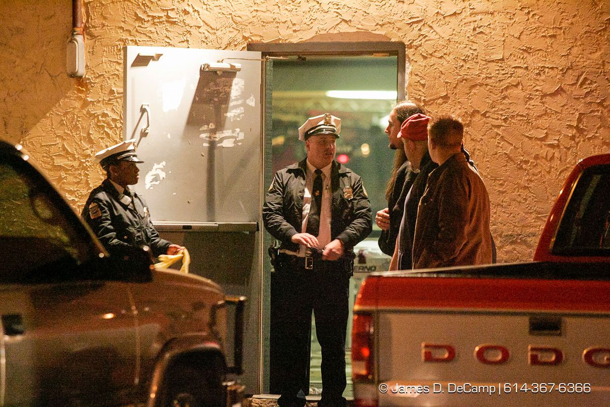 Columbus Police guard the doors from the parking lot as Columbus, Worthington & Clinton Twp Medics work on one of seven shooting victims at the Alrosa Villa, 5055 Sinclair Road late Wednesday night December 8, 2004. (© James D. DeCamp | http://www.JamesDeCamp.com | 614-367-6366)