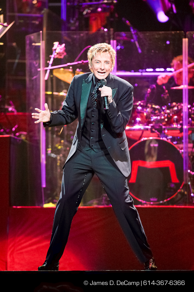 "Barry Manilow wows the crowd gathered at Nationwide Arena Friday night February 8, 2008 during the local stop in his ""Music & Passion"" tour. Barry Manilow is an American singer-songwriter and producer. He is best known for such recordings as ""Mandy"", ""Can't Smile Without You"", and ""Copacabana (At the Copa)"". In 1978, five of his albums were on the best-seller charts simultaneously, a feat equalled only by Herb Alpert, The Beatles, Frank Sinatra, Michael Jackson, Bruce Springsteen, and Johnny Mathis. He has recorded a string of Billboard hit singles and multi-platinum albums that have resulted in his being named Radio & Records' No. 1 adult contemporary artist, and winning three straight American Music Awards for favorite pop/rock male artist. Between 1974 and 1983 Manilow had three No. 1 singles and 25 that reached the top 40. Although not a favorite of music critics, several well-known entertainers have praised Manilow, including Sinatra, who was quoted in the 1970s saying, ""He's next."" In 1988, Bob Dylan stopped Manilow at a party, hugged him and said, ""Don't stop what you're doing, man. We're all inspired by you."" (© James D. DeCamp 