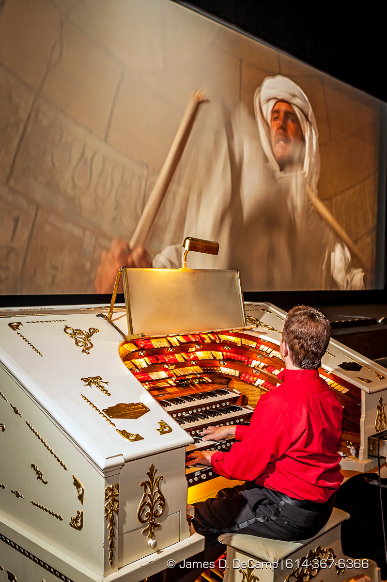 "Clark Wilson, CAPA Organist poses for a portrait Saturday June 18, 2016 at the Ohio Theatre. The Organ Wilson plays during the CAPA Summer Movie Series is called the 'Mighty Morton' and was installed in the theatre in 1928. Powered by a 25-horsepower turbine-type blower beneath the stage, the organ is raised and lowered by a screw-driven, enabling it to be ""hidden"" during other performances. and is comprised of more than 2,500 pipes. (© James D. DeCamp 