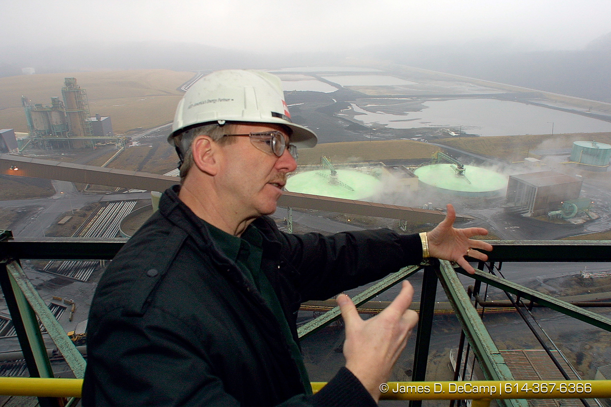 Conesville Power plant Manager Daniel Lambert describes some of the processes involved in using coal as a power source. Behind him in the dark rectangular ponds is a slurry of slag and fly ash from the plants boilers and scrubbers. Fly ash, a complex composition of silicon and aluminum oxides together with oxides of iron, calcium, titanium, potassium and trace metals, originates from residual inorganic matter contained in coal. When coal is burned in steam generators, the matter is fused and carried with flue gas as the carbon is consumed by oxidation. The flue gas cools as it flows out of the steam generator, and the molten ash takes the form of ceramic particles. The ash particles are collected in electrostatic precipitators. In the green circular tanks is Calcium Sulfate, a product of the smoke stack scrubber used at the plant to limit air pollution. Scrubbers operate by spraying a mixture of pulverized limestone and water into the exhaust gas of the generating units. Inside the scrubber vessels, calcium in the limestone reacts with the gaseous SO2 to form calcium sulfate, commonly know as gypsum. (© James D. DeCamp | http://www.JamesDeCamp.com | 614-367-6366) [Photographed with Canon EOS D30 cameras with L series lenses.]