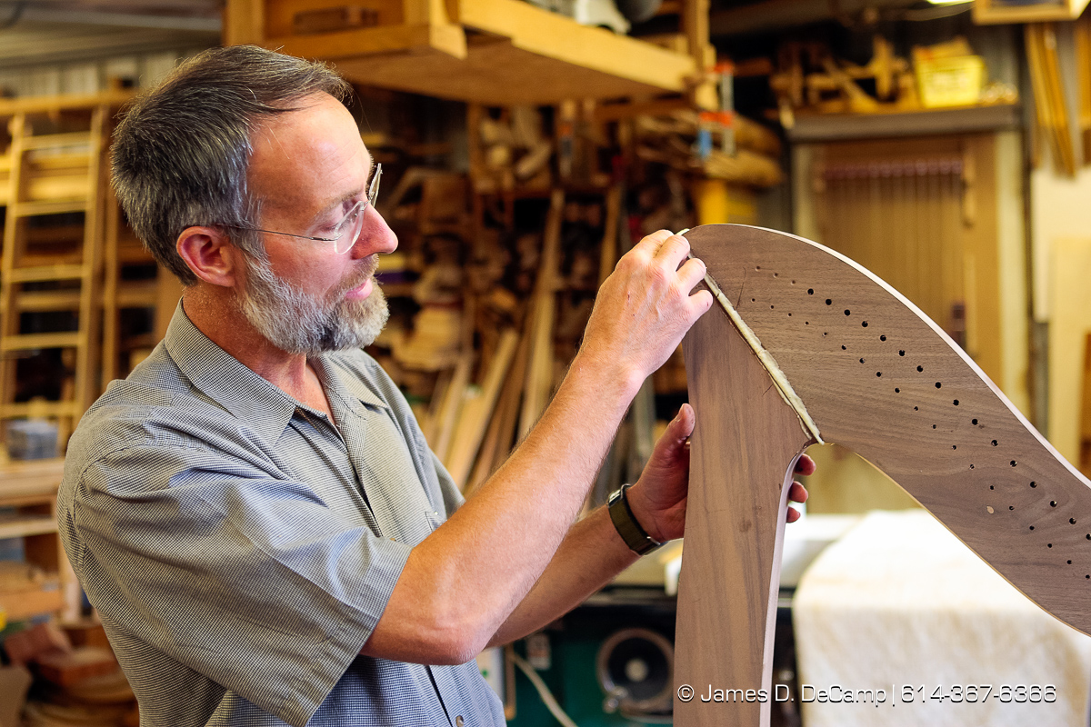 Reuben Hosteler inspects the neck of a Harp in progress photographed Wednesday evening October 1, 2008 at the Hostetler's workshop north of Coshocton. (© James D. DeCamp | http://www.JamesDeCamp.com | 614-367-6366) [Photographed with Canon 1D MkIII cameras in RAW mode with L series lenses]
