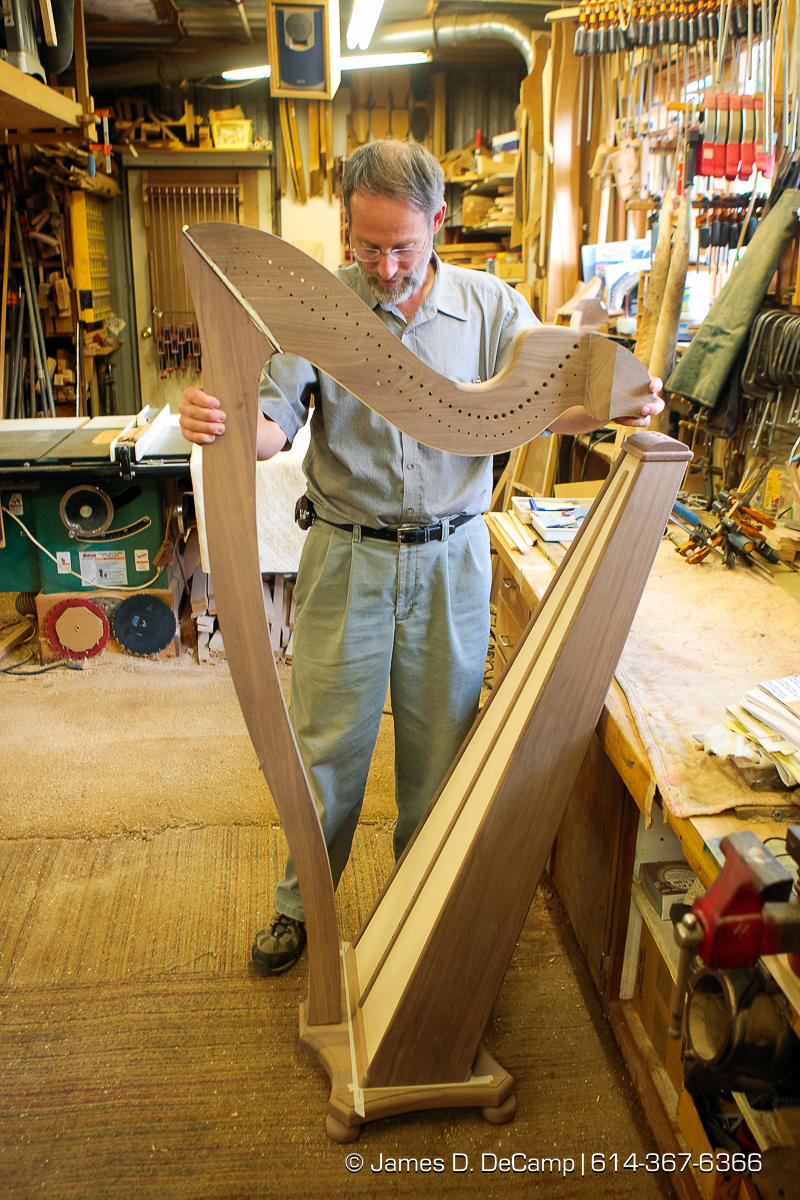 Reuben Hosteler inspects the neck of a Harp in progress photographed Wednesday evening October 1, 2008 at the Hostetler's workshop north of Coshocton. A hand painted rock marks the long driveway to the Hostetler's Harp's of Praise workshop and home photographed Wednesday evening October 1, 2008. (© James D. DeCamp | http://www.JamesDeCamp.com | 614-367-6366) [Photographed with Canon 1D MkIII cameras in RAW mode with L series lenses]