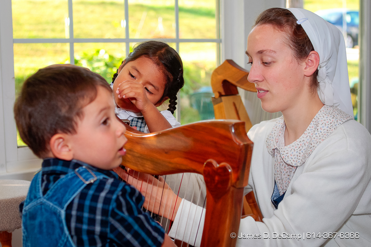Darlene Hostetler, right, gets some 'help' in tuning a harp from little brother and sister Jonathan, 2, and Jewell, 3, photographed Wednesday evening October 1, 2008 at the Hostetler's home north of Coshocton. (© James D. DeCamp | http://www.JamesDeCamp.com | 614-367-6366) [Photographed with Canon 1D MkIII cameras in RAW mode with L series lenses]