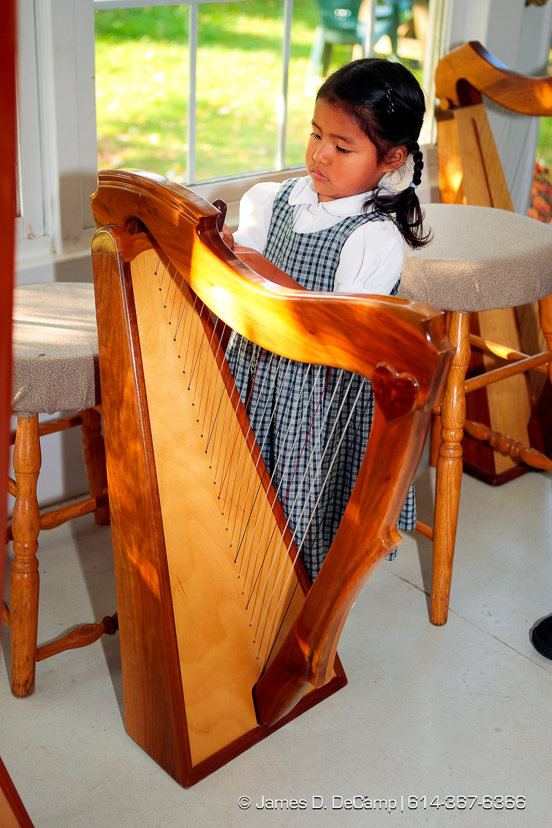 Jewell Hostetler, 3, tries her hand at tuning a harp photographed Wednesday evening October 1, 2008 at the Hostetler's home north of Coshocton. (© James D. DeCamp | http://www.JamesDeCamp.com | 614-367-6366) [Photographed with Canon 1D MkIII cameras in RAW mode with L series lenses]