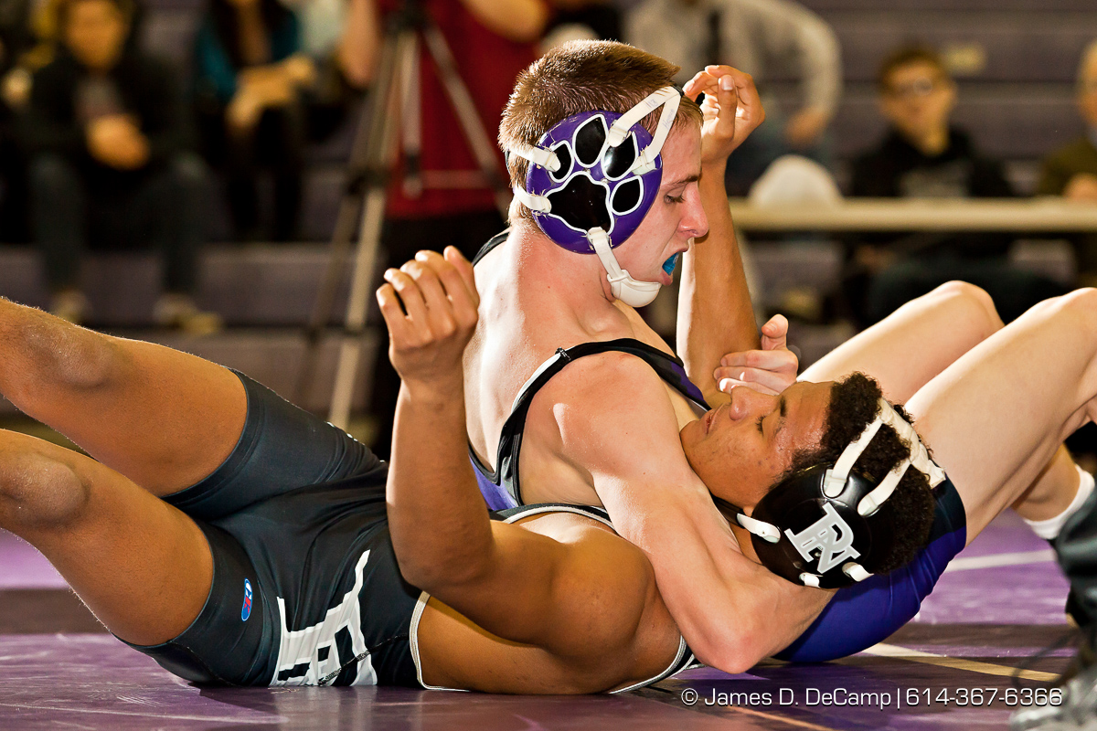 Pickerington North High School's Ahmad Taylor wrestles with Pickerington Central High School's Tyler Hogue in the 113 lb. weight class Thursday evening February 2, 2012 at Pickerington North High School. (© James D. DeCamp | http://www.JamesDeCamp.com | 614-367-6366)