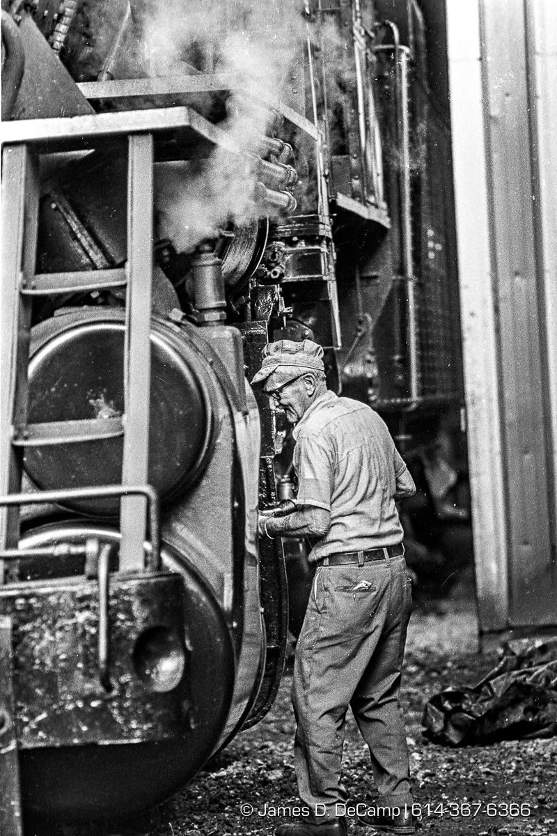 Ross Ballard works on the Hocking Valley Scenic Railway's Engine #33 Saturday, October 1, 1983 in Nelsonville, Ohio. The steam engine, an ex-Lake Superior & Ishpeming Railroad Baldwin 2-8-0 was restored over several years in the 1960's. Engine #33 sat in a Columbus Ohio railroad yard until trackage became available in Nelsonville in 1972. This is the original steam locomotive of the HVSRy. The famous Baldwin Locomotive Works built several of these big freight engines in 1916 for the Lake Superior & Ishpeming Railroad which hauled iron ore in upper Michigan. The Hocking Valley Scenic Railway is a non-profit, 501c3, volunteer-operated tourist railroad attraction that operates out of Nelsonville, Athens County, Ohio. It is also located near the popular Hocking Hills State Park in nearby Hocking County. It uses former trackage of the Chesapeake & Ohio Railway, which was in turn originally Hocking Valley Railway trackage. The current operation was founded in 1972. (© James D. DeCamp | http://JamesDeCamp.com | 614-367-6366) [Shot on Kodak Tri-X film. Processed with Kodak Microdol-X Developer. Digitized with a Nikon Coolscan 4000 ED]