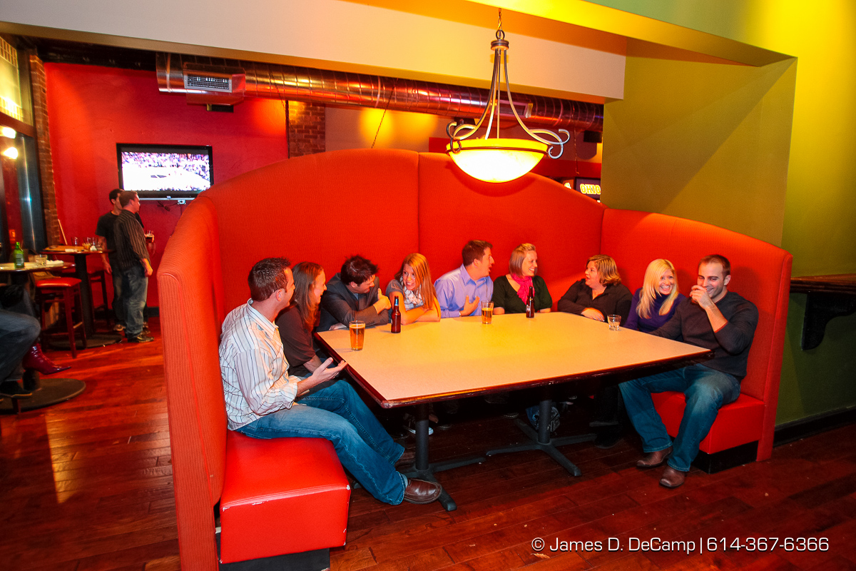 A group hangs out in one of the big booths at the Harrison's on Third bar Friday night November 7, 2008. (© James D. DeCamp | http://www.JamesDeCamp.com | 614-367-6366) [Photographed with Canon 1D MkIII cameras in RAW mode with L series lenses]