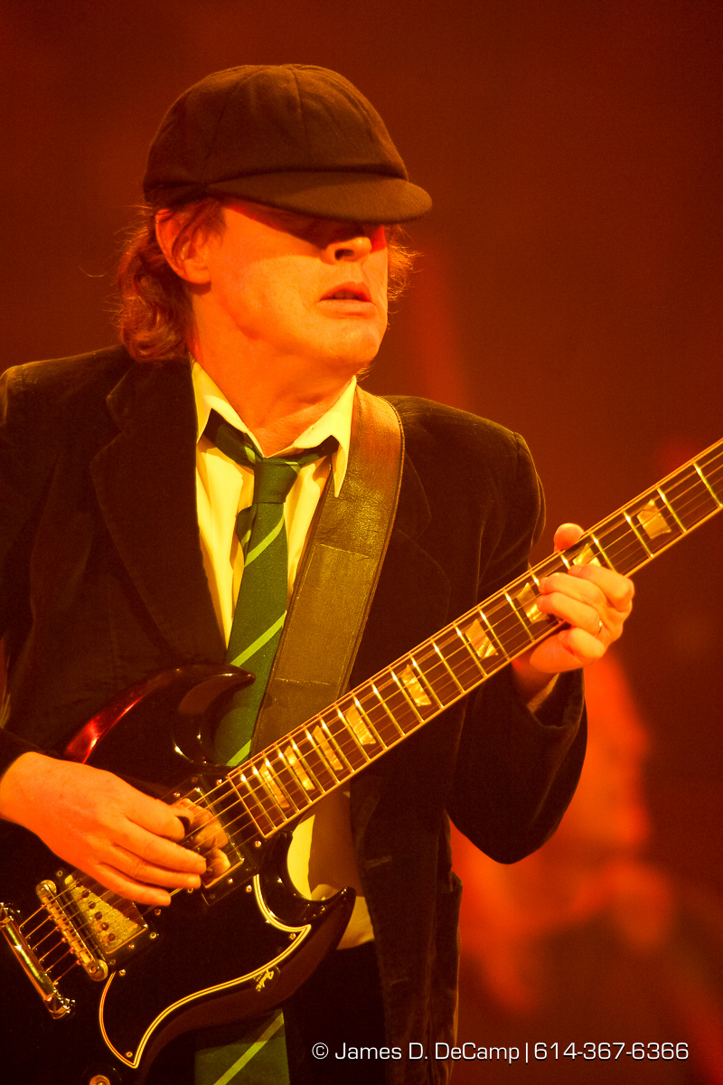 "AC/DC perform for a capacity crowd at the Jerome Schottenstein Center's Value City Arena Friday night November 21, 2008. AC/DC are an Australian hard rock band, formed in November 1973 by brothers Malcolm and Angus Young, who continued as members until Malcolm's illness and departure in 2014. Commonly referred to as a hard rock or blues rock band, they are also considered pioneers of heavy metal and are sometimes classified as such, though they have always dubbed their music as simply ""rock and roll"". To date they are one of the best-selling bands of all time, with a total of more than 200 million albums sold worldwide. AC/DC underwent several line-up changes before releasing their first album, High Voltage, on 17 February 1975; Malcolm and Angus were the only original members left in the band. Membership subsequently stabilized until bassist Mark Evans was replaced by Cliff Williams in 1977 for the album Powerage. Within months of recording the album Highway to Hell, lead singer and co-songwriter Bon Scott died on 19 February 1980 after a night of heavy alcohol consumption. The group considered disbanding, but buoyed by support from Scott's parents, decided to continue and set about finding a new vocalist. Ex-Geordie singer Brian Johnson was auditioned and selected to replace Scott. Later that year, the band released the new album, Back in Black, which was made as a tribute to Bon Scott. The album launched them to new heights of success and became their all time best-seller, selling over 10,000 copies per day in its first week. (© James D. DeCamp 
