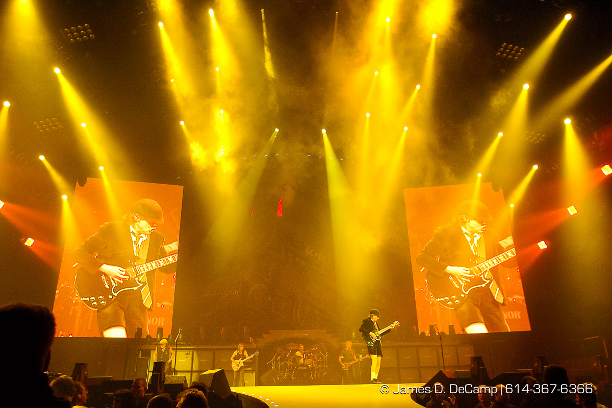 """AC/DC perform for a capacity crowd at the Jerome Schottenstein Center's Value City Arena Friday night November 21, 2008. AC/DC are an Australian hard rock band, formed in November 1973 by brothers Malcolm and Angus Young, who continued as members until Malcolm's illness and departure in 2014. Commonly referred to as a hard rock or blues rock band, they are also considered pioneers of heavy metal and are sometimes classified as such, though they have always dubbed their music as simply """"rock and roll"""". To date they are one of the best-selling bands of all time, with a total of more than 200 million albums sold worldwide. AC/DC underwent several line-up changes before releasing their first album, High Voltage, on 17 February 1975; Malcolm and Angus were the only original members left in the band. Membership subsequently stabilized until bassist Mark Evans was replaced by Cliff Williams in 1977 for the album Powerage. Within months of recording the album Highway to Hell, lead singer and co-songwriter Bon Scott died on 19 February 1980 after a night of heavy alcohol consumption. The group considered disbanding, but buoyed by support from Scott's parents, decided to continue and set about finding a new vocalist. Ex-Geordie singer Brian Johnson was auditioned and selected to replace Scott. Later that year, the band released the new album, Back in Black, which was made as a tribute to Bon Scott. The album launched them to new heights of success and became their all time best-seller, selling over 10,000 copies per day in its first week. (© James D. DeCamp   http://www.JamesDeCamp.com   614-367-6366) [Photographed with Canon 1D MkII cameras in RAW mode with L series lenses]"""