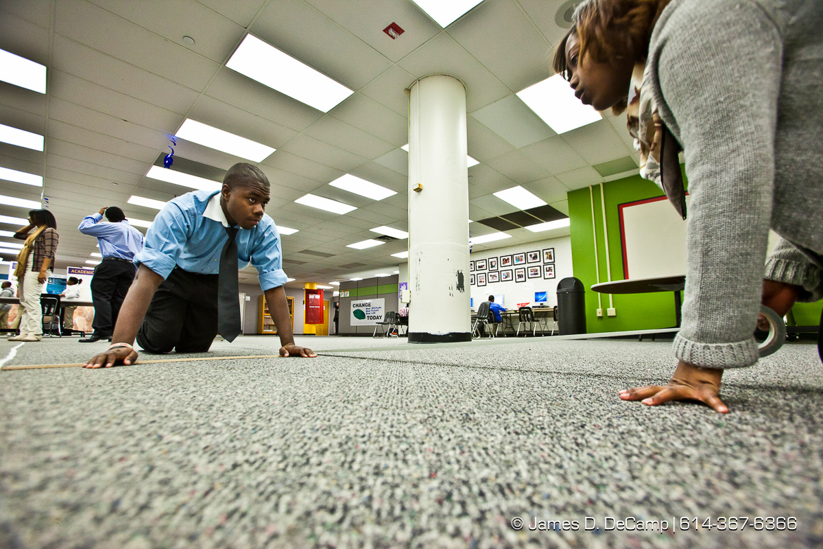 Lesley Johnson, left, and Jonetta White, right, put tape down don the floor of the commons area of the Dayton Early College Academy early Wednesday morning December 15, 2010 to form a runway for a 'stereotypes' fashion show later in the day. (© James D. DeCamp   http://www.JamesDeCamp.com   614-367-6366)