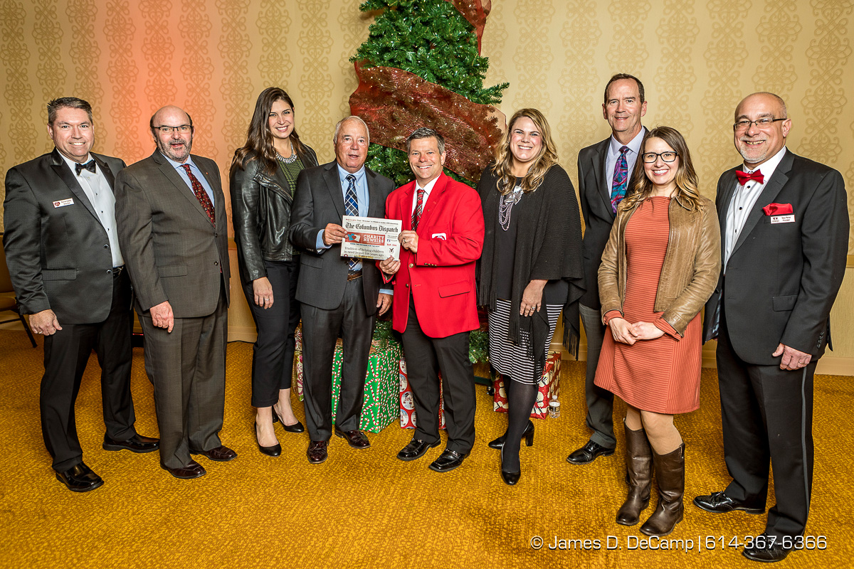 The first newspaper in the The 2017 Clothe-a-Child Gala and 110th annual Charity Newsies Newspaper Auction was sold to Nationwide Insurance: (l-r) Pat Conley, Stephen Chandler, AuBree Lucas, Jim Simpson, Kirk Smith, Allyson Lash, Jim Guinan, Jody Geiger, and Tony Perez photographed Thursday, November 30, 2017 at the Hollywood Casino Ballroom. (© James D. DeCamp | http://JamesDeCamp.com | 614-367-6366)