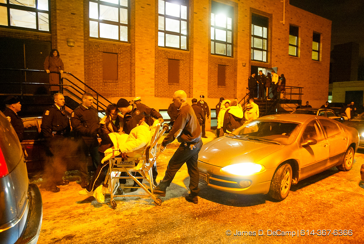 A woman is loaded into a stretcher/wheelchair outside of the gymnasium of Linden-McKinley High School by Columbus Paramedics after a fight broke out at the end of the schools basketball game against Beechcroft High School late Tuesday night January 27, 2004. According to paramedics the woman was suffering from exposure to Mace® used by Columbus Police in the gymnasium to try and break up a fight. Four people were treated for use of Mace®, one for a heart attack, and one with an asthma attack. (© James D. DeCamp | http://www.JamesDeCamp.com | 614-367-6366) [Photographed with Canon 1D MkII cameras in RAW mode with L series lenses]