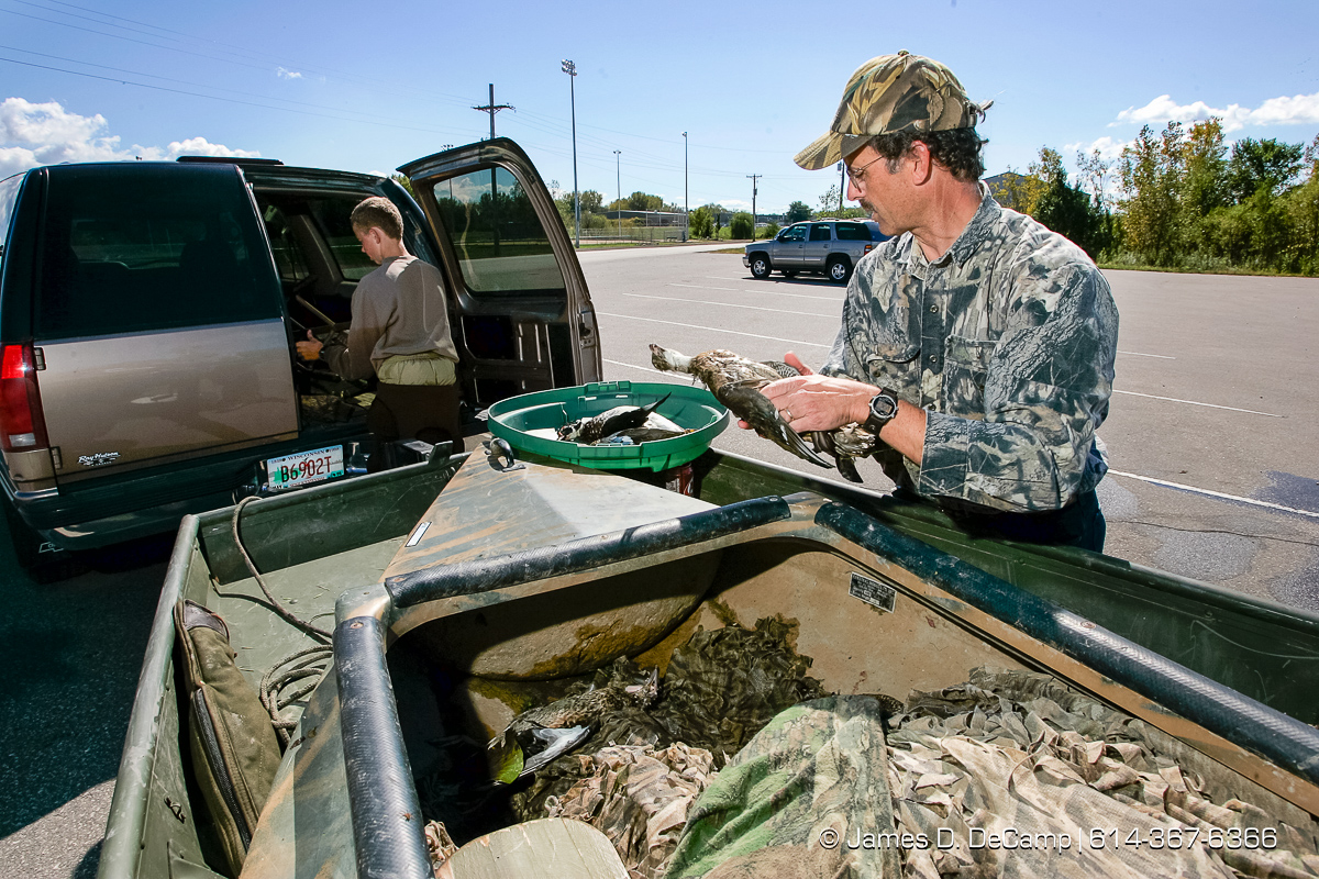 Jeff Conway counts his kill of ducks as his son Adam packs up after a morning of duck hunting just south of La Crosse Wisconsin along the Missouri River during day 2 of the 2004 'Real People Tour' of middle America. (© James D. DeCamp | http://www.JamesDeCamp.com | 614-367-6366) [Photographed with Canon 1D MkII cameras in RAW mode with L series lenses]