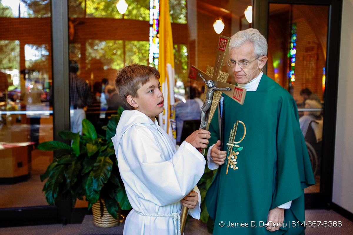 Father Donald P. Schmitz, right, talks with Shane McCabe, 10, before the start of Mass at the Church of the Nativity in Harmony Minnesota photographed Sunday September 26, 2004 on day 3 of the 2004 'Real People Tour' of middle America. (© James D. DeCamp | http://www.JamesDeCamp.com | 614-367-6366) [Photographed with Canon 1D MkII cameras in RAW mode with L series lenses]