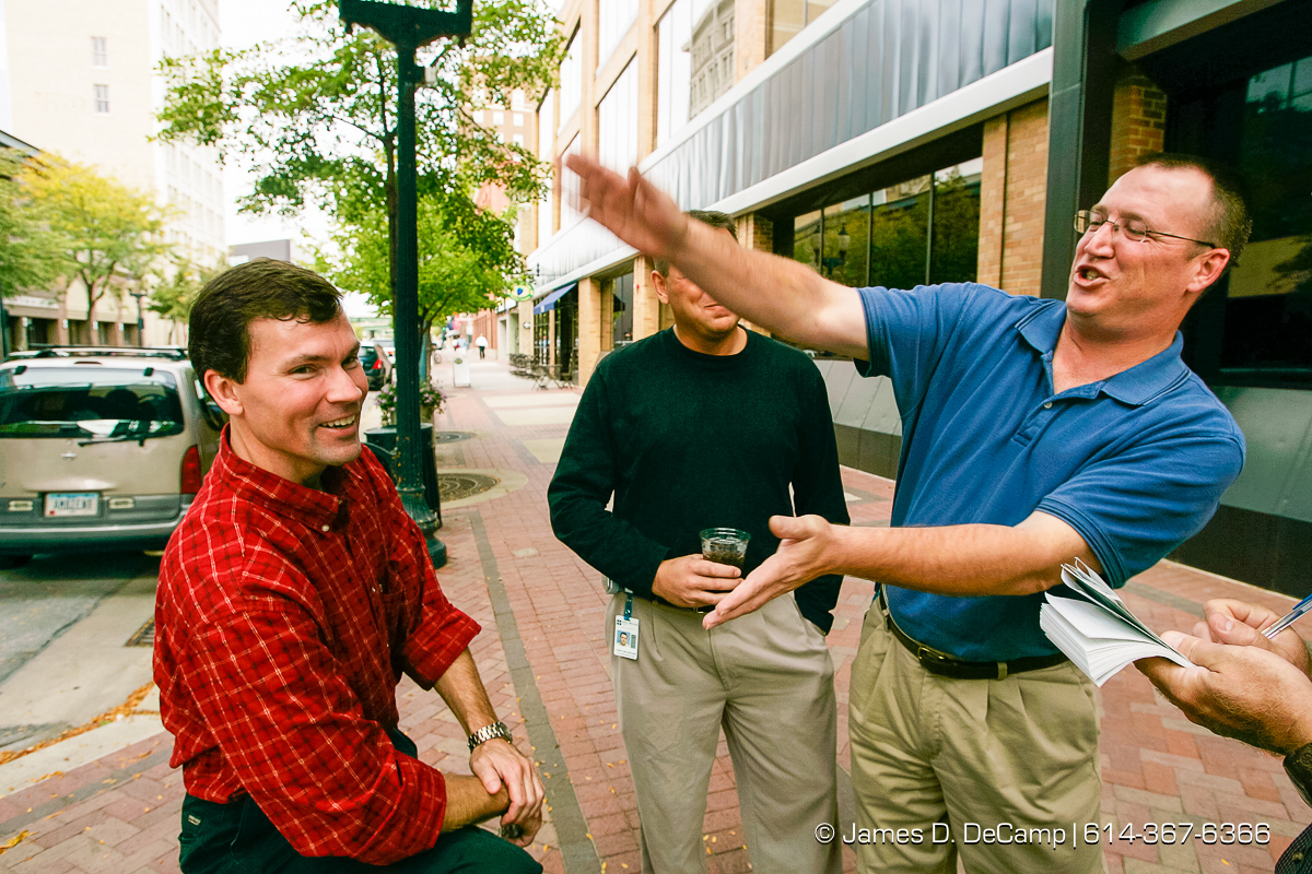 Brent Thomas, right, a Bush supporter playfully slaps Mark Gruca, left, when he said that he would be voting for Kerry in downtown Cedar Rapids, Iowa on day 4 of the 2004 'Real People Tour' of middle America. In the rear is Christopher Kircher. (© James D. DeCamp | http://www.JamesDeCamp.com | 614-367-6366) [Photographed with Canon 1D MkII cameras in RAW mode with L series lenses]