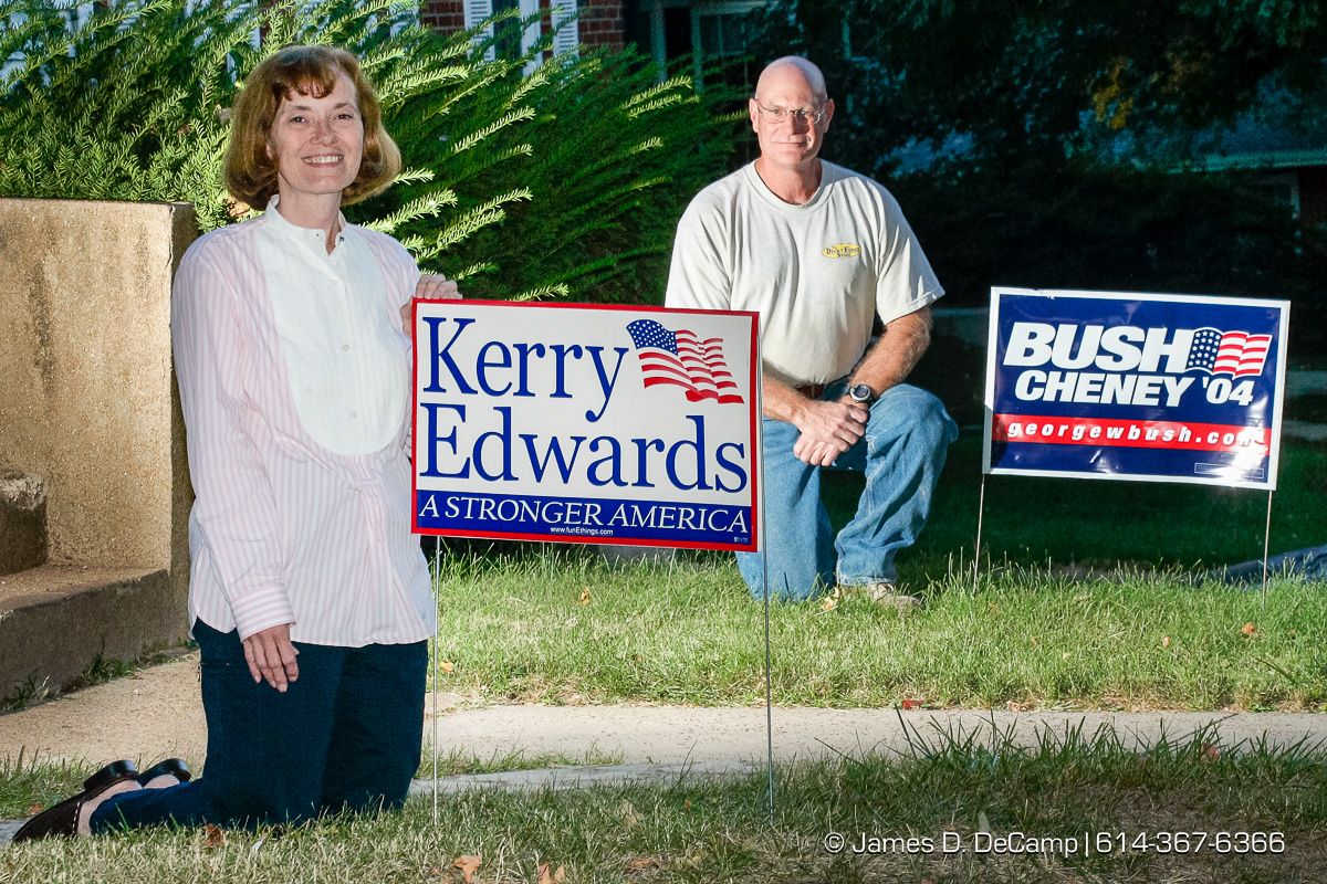 Husband and wife Miriam foreground, and Jerry Miramonti agree to disagree on their choice for president, kneeling next to opposing signs that they have in their Shrewsbury, Missouri front yard photographed Wednesday September 29, 2004 on day 6 of the 2004 'Real People Tour' of middle America. (© James D. DeCamp | http://www.JamesDeCamp.com | 614-367-6366) [Photographed with Canon 1D MkII cameras in RAW mode with L series lenses]