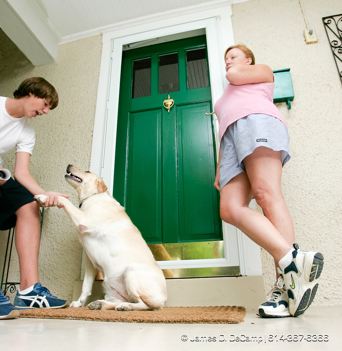 Bush supporters Shannon Gorman, right, talks with us as her son Patrick, 14, plays with their Lab Lucy ion the front porch of their house along South Gore Avenue photographed Wednesday September 29, 2004 on day 6 of the 2004 'Real People Tour' of middle America. (© James D. DeCamp | http://www.JamesDeCamp.com | 614-367-6366) [Photographed with Canon 1D MkII cameras in RAW mode with L series lenses]
