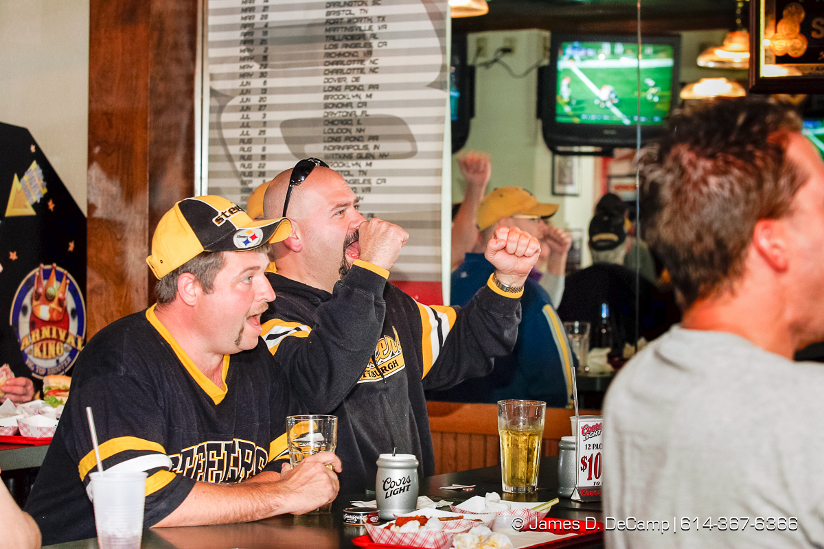 Chuck Bardwell, left, and Tim Helsley celebrate a Pittsburgh Steelers touchdown at Scorchers Casual Eatery & Draft House in Erie, PA Sunday October 3, 2004 on day 10 of the 2004 'Real People Tour' of middle America. (© James D. DeCamp | http://www.JamesDeCamp.com | 614-367-6366) [Photographed with Canon 1D MkII cameras in RAW mode with L series lenses]