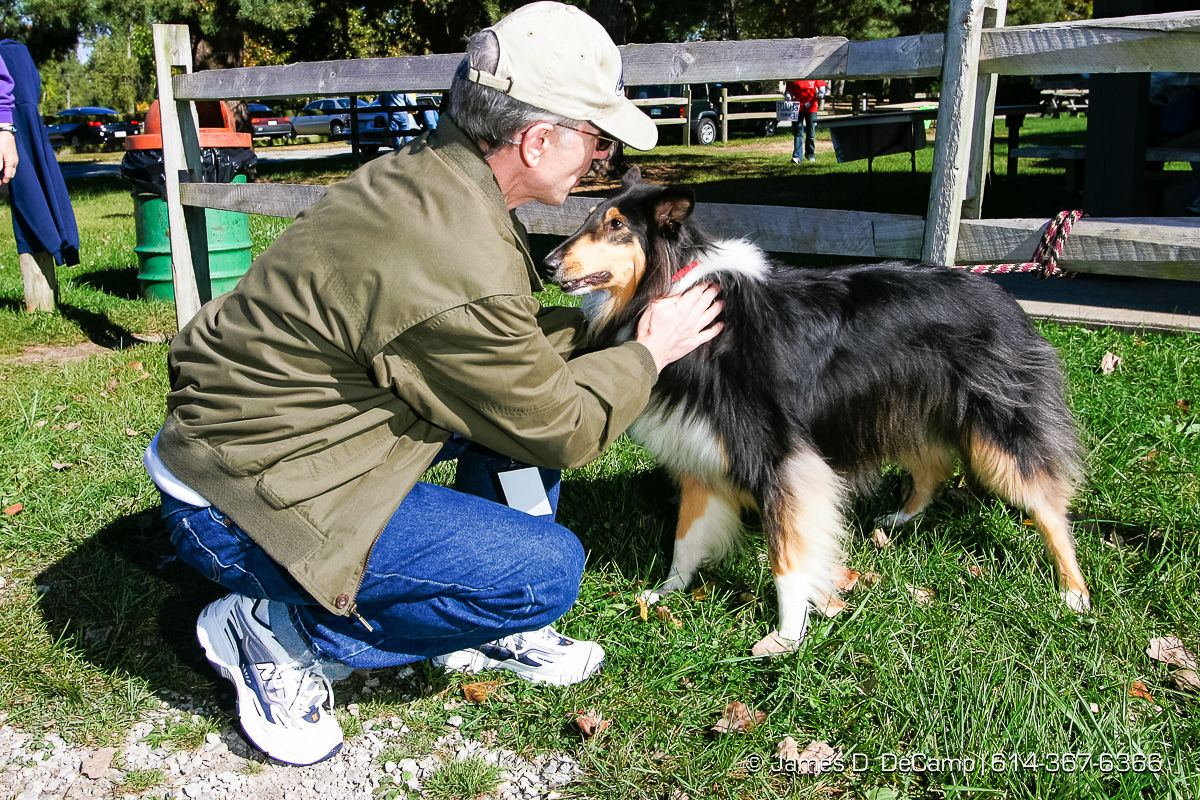 Mark Vatavuk, a volunteer, pets one of the rescue dogs at a Dog Walk Athon for the Because You Care Dog Rescue Shelter on the Presque Isle State Park in Erie, PA Sunday October 3, 2004 on day 10 of the 2004 'Real People Tour' of middle America. (© James D. DeCamp | http://www.JamesDeCamp.com | 614-367-6366) [Photographed with Canon 1D MkII cameras in RAW mode with L series lenses]